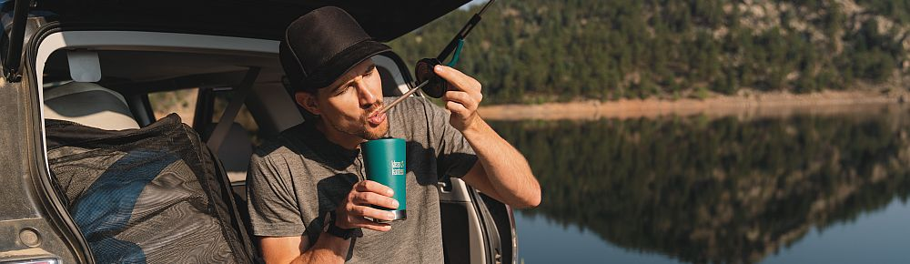 Mann sitzt am Rand seines Kofferraums an einem See und trinkt aus einem Klean Kanteen Strohhalm.