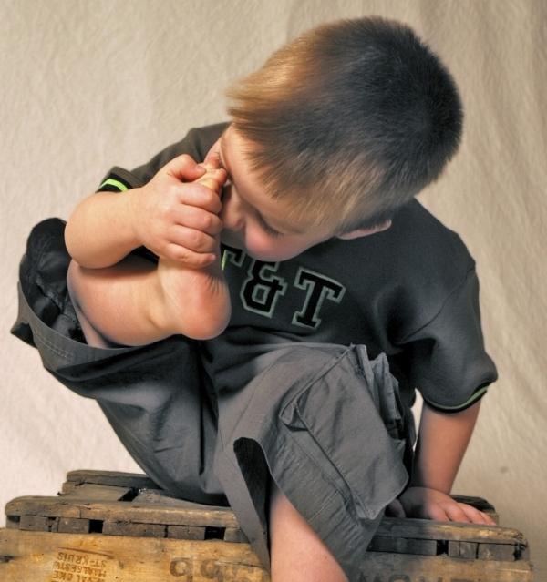 Kind riecht am Fuß