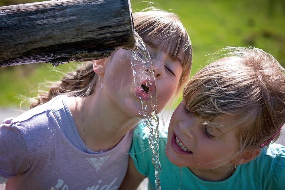 Kinder trinken Brunnenwasser