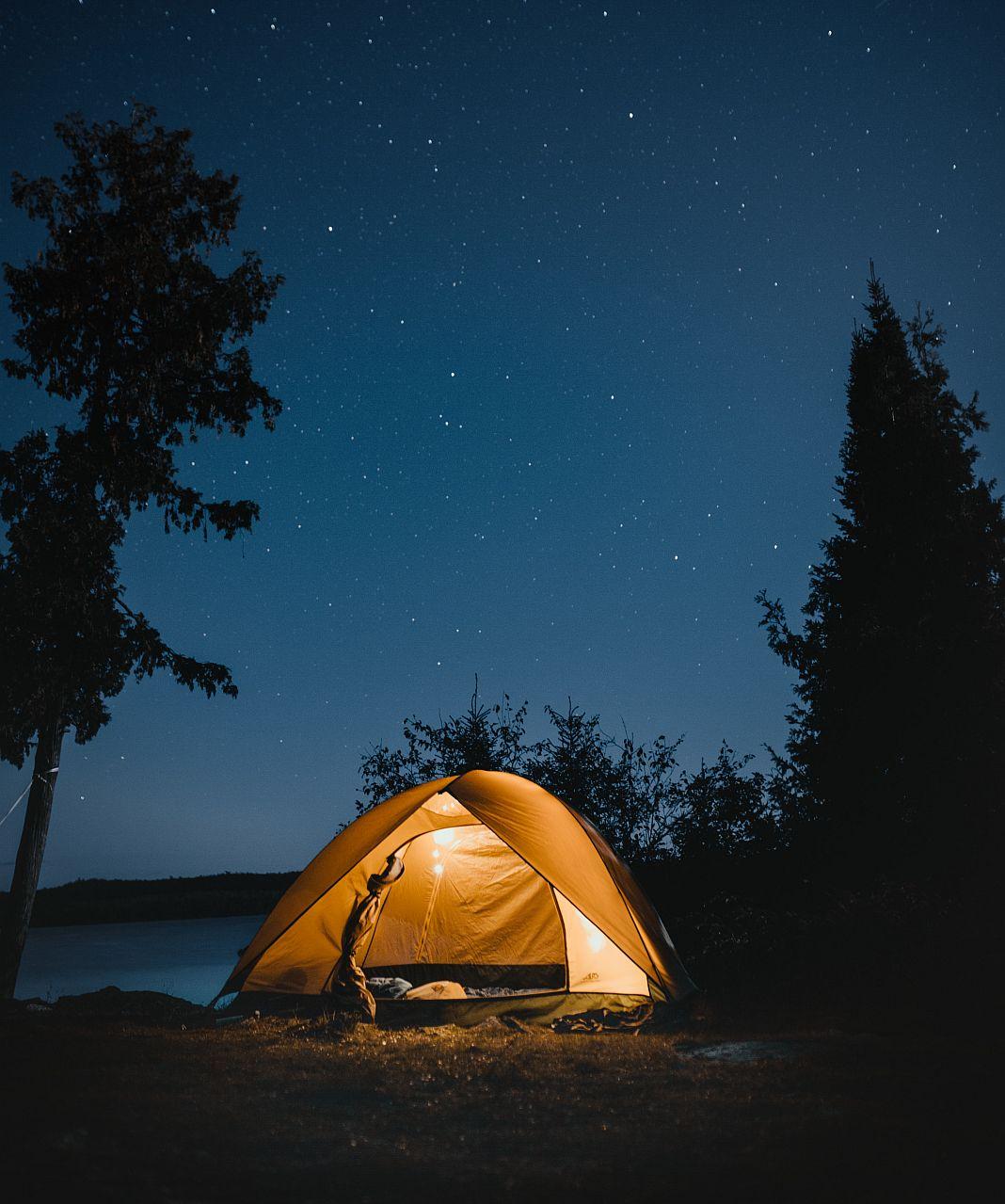 Aufgebautes Zelt bei Nacht unter sternenklarem Himmel.
